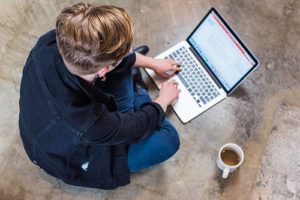 image of a business owner writing a blog post on their laptop to reinforce how writing a blog is good for business