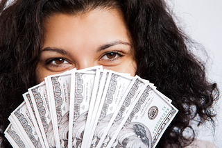image of a woman holding fanned out hundred dollar bills to illustrate the importance of knowing how to calculate the ROI of your seocial media marketing effortste