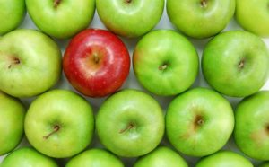 image of a red apple amongst a batch of green apples to illustrate that if you want to stand out from the competition you need to market a point of difference about your company, product or service